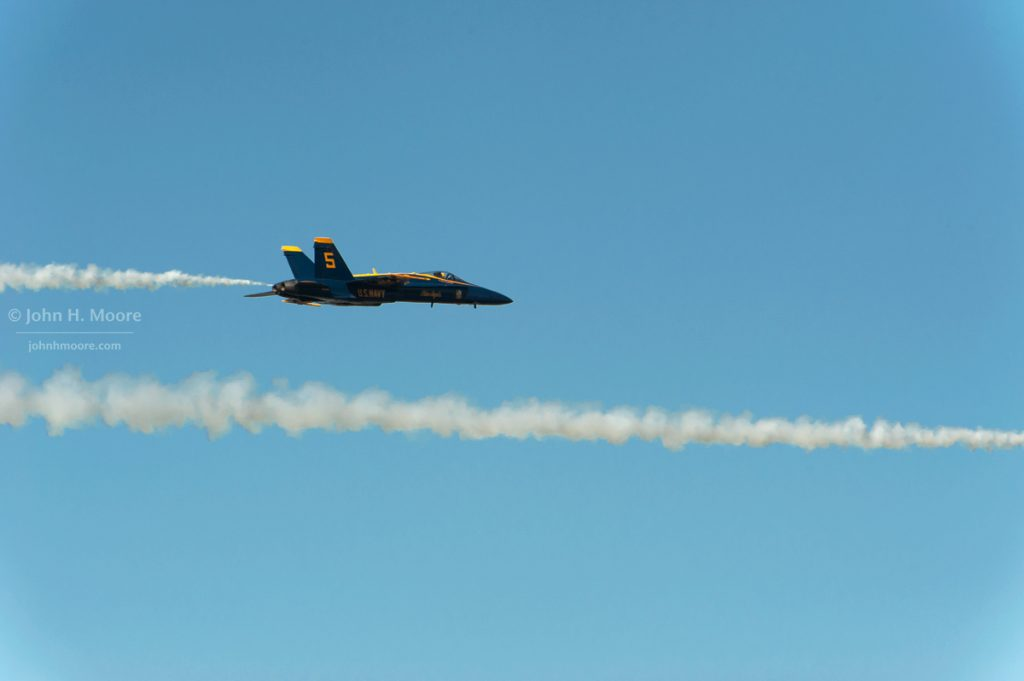 Blue Angel #5 crosses above the smoke trail just laid by Blue Angel #6. 2016 Miramar Air Show.  San Diego, California, USA.