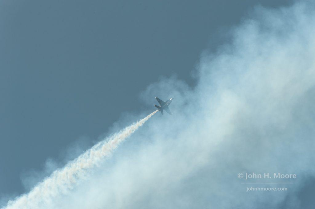 A Blue Angel crosses back behind its own smoke.  2016 Miramar Air Show.  San Diego, California, USA.